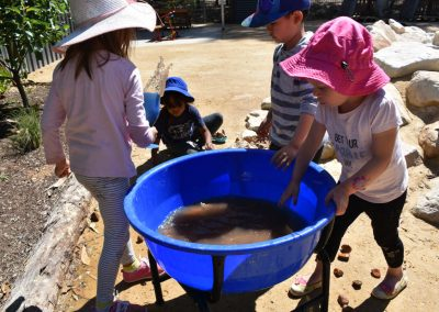 four-children-playing-with-mud-in-blue-container