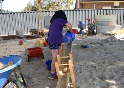 Girl playing in sandpit with conveyor sand